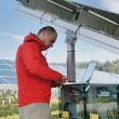 Engineer using laptop at solar panels plant field — Stock Photo #8994276