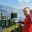 Engineer using laptop at solar panels plant field — Stock Photo #8994297