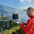 Photo: Engineer using laptop at solar panels plant field
