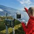 Engineer using laptop at solar panels plant field — Stock Photo #8994357