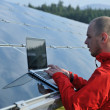 Engineer using laptop at solar panels plant field — Foto Stock