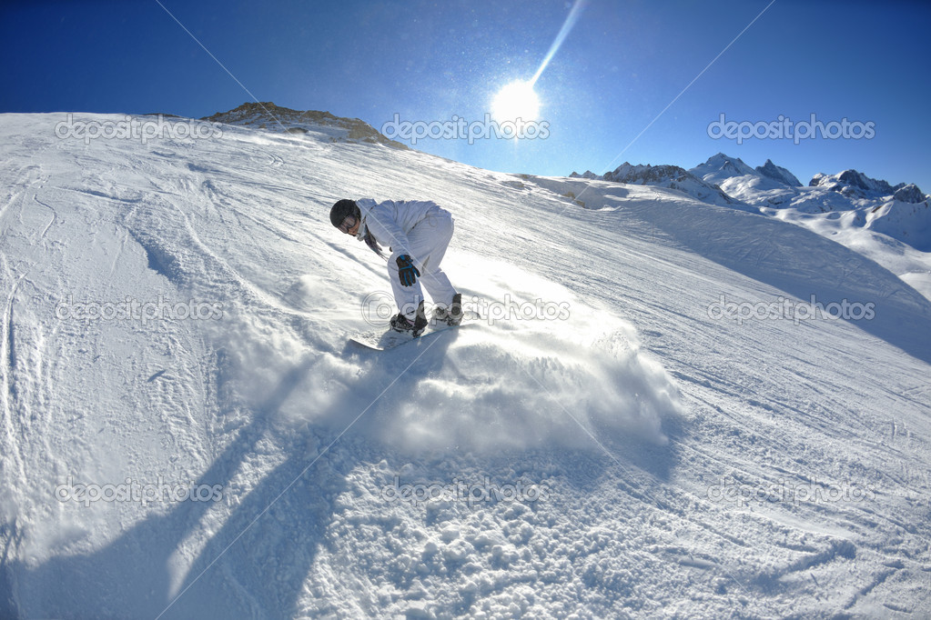 Skier skiing downhill on fresh powder snow  with sun and mountains in background — Stock Photo #9217807