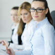 Business woman standing with her staff in background — Stockfoto