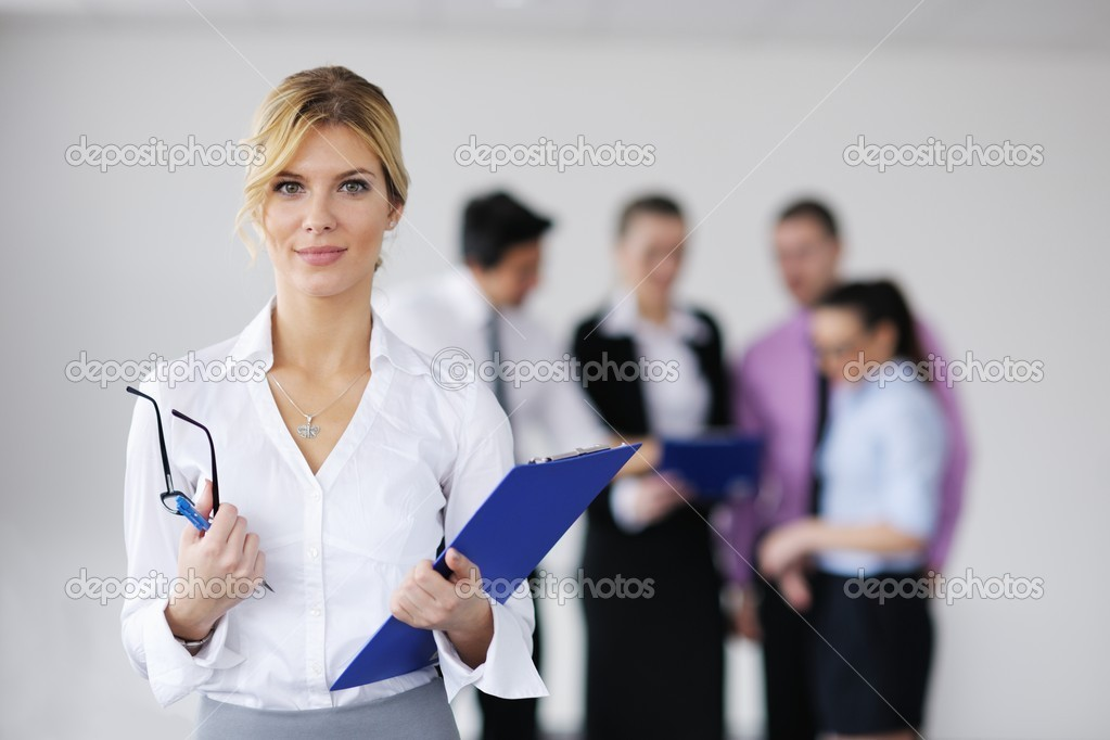 Successful business woman standing with her staff in background at modern bright office — Stock Photo #9433666