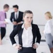Business woman standing with her staff in background — Stock Photo #9567438