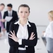 Business woman standing with her staff in background — Stock Photo #9567546