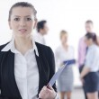 Business woman standing with her staff in background — Stock Photo #9568614