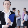 Business woman standing with her staff in background — Stock Photo #9568626