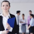 Business woman standing with her staff in background — Stock Photo #9568631