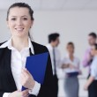 Business woman standing with her staff in background — Stock Photo #9568661