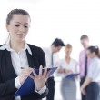 Business woman standing with her staff in background — Stock Photo #9568674