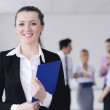 Business woman standing with her staff in background — Stock Photo #9568684