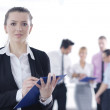 Business woman standing with her staff in background — Stock Photo #9568688