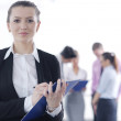 Business woman standing with her staff in background — Stock Photo #9568694