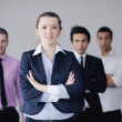 Business woman standing with her staff in background — Stock Photo #9569972