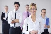 γυναίκα των επιχειρήσεων στέκεται με το προσωπικό στο παρασκήνιο — Φωτογραφία Αρχείου