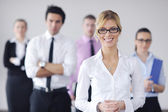 Business woman standing with her staff in background — Foto Stock