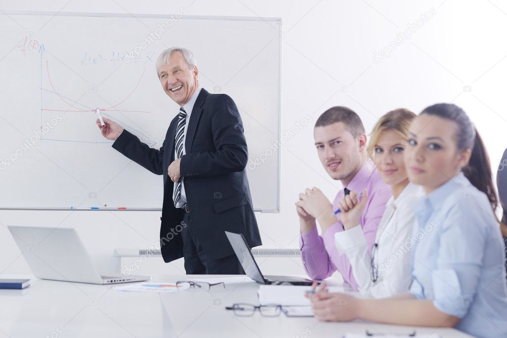 Senior male business man giving a presentation at a  meeting at modern light office on a table board  Stock Photo #9568284