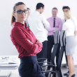 Business woman standing with her staff in background — Stock Photo #9570121
