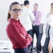 Business woman standing with her staff in background — Stock Photo #9570132