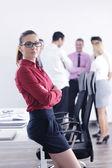Obchodní žena stojící s její zaměstnanci v pozadí — Stock fotografie