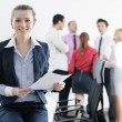 Business woman standing with her staff in background — Stock Photo