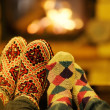 Young romantic couple sitting on sofa in front of fireplace at home — Stockfoto