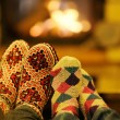 Young romantic couple sitting on sofa in front of fireplace at home — Stock fotografie