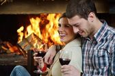 Young romantic couple sitting on sofa in front of fireplace at h — Photo