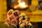 Young romantic couple sitting on sofa in front of fireplace at home — Stok fotoğraf