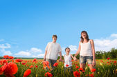 Family in red poppy field — Stock Photo