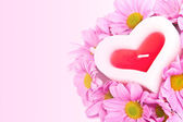 Candle in the shape of a heart and chrysanthemums. — Stock Photo