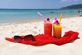 Pair of fruit shakes, red shawl and sunglasses on the beach of P — Stock Photo