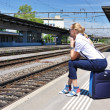 Girl at the railway station waiting for a train - Foto Stock