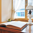 Stock Photo: Old petroleum-lamp and book against window