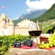 Stock Photo: Red wine and grapes against old castle. Switzerland