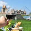 Two hands holding wineglasses against Chateau d'Aigle, Switzerla — Stock Photo