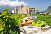 Wine, grapes and bread against old castle. Switzerland — Stock Photo