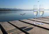Two champagne glasses against a lake — Stockfoto