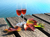 Two winglasses and autumn leaves on a wooden jetty — Foto de Stock
