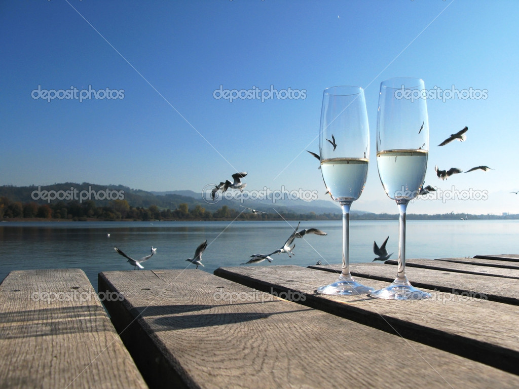 Two champaign glasses against a lake — Stock Photo #8300616
