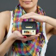 Woman with miniature house on black background — Stok fotoğraf
