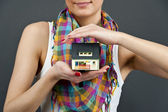 Woman with miniature house on black background — Stock Photo