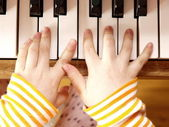 Close up of child's hands playing the piano — Stock Photo