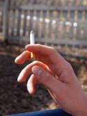 A close-up of fingers holding a cigarette — Stock Photo