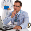 Male doctor with nurse in the background — Stock Photo #8992116
