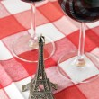 Little Eiffel tower and pair of wineglasses on table — Stock Photo #8297198