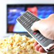 Remote control in the hand against pop-corn and TV-set — Stock Photo #8297206