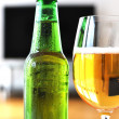 Glass of beer and a bottle against TV-set - Stok fotoraf