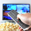 Remote control in hand against pop-corn and TV-set — Stock Photo #8297366